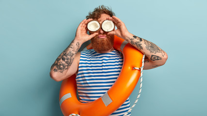 Curly red haired man keeps cocnonut on eyes, has fun near water, feels bored working as liveguard, wears sailor vest, stands over blue background, carries orange lifebuoy for saving people at beach
