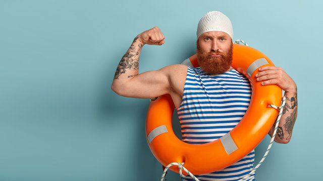 Self confident strong male lifeguard shows muscles, raises arm, has serious expression, carries safety ring, cares about water safety, helps swimmers who are in trouble, responds on aquatic emergency