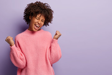 Efforts finally brought success. Overjoyed dark skinned woman celebrates victory and clenches fists, shouts hooray, triumphs over win, cheers good results, isolated over purple studio background.