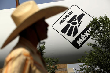 "A man passes in front of a logo that says ""Made in Mexico"", in Ciudad Juarez"