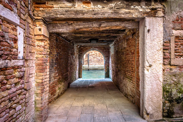 Fototapete - Exit to the water canal from courtyard, Venice, Italy. Vintage corridor of yard of residential area. Ancient architecture of Venice. Old street of the Venice city. Antique pedestrian brick tunnel.