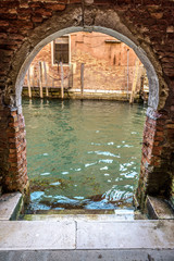 Fototapete - Exit to the canal from courtyard, Venice, Italy. Vintage entrance to the yard of residential house. Ancient architecture of Venice. Stairs to the water and old street of the Venice city.