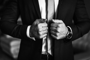 Man in business suit. A man puts on a suit. Close-up business stylish man buttoning his jacket. A businessman in an expensive suit.  Black and white photo