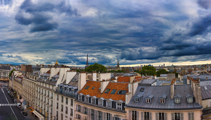 Wall Mural - Paris roofs with Eiffel Tower and other buildings under dramatic sky