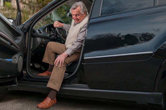 Senior man having  pain in hte knee while getting out of his car