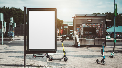 Mockup of an empty urban advert poster surrounded by scooters scattered across the street on the pavement stone; template of a blank street information billboard with a newsstand in the background