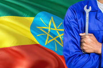 Ethiopian Mechanic in blue uniform is holding wrench against waving Ethiopia flag background. Crossed arms technician.