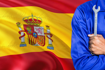 Spanish Mechanic in blue uniform is holding wrench against waving Spain flag background. Crossed arms technician.