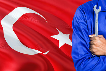 Turkish Mechanic in blue uniform is holding wrench against waving Turkey flag background. Crossed arms technician.