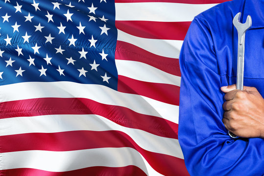 American Mechanic in blue uniform is holding wrench against waving United States of America flag background. Crossed arms technician.