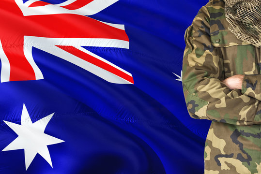 Crossed arms soldier with national waving flag on background - XXX Military theme.