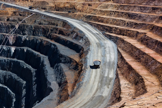 Two trucks transport gold ore from open cast mine. Barrick Cowal Gold Mine in New South Wales,  Australia.