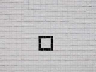 black square on a white tiled wall