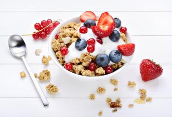 Granola with yogurt, muesli and berries on white wood background