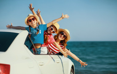 happy family mother and children girls goes to summer travel trip in car.