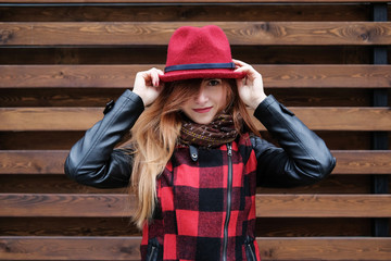 Sensual woman in a red bowler hat with long hair on wooden background. Autumn fashion.