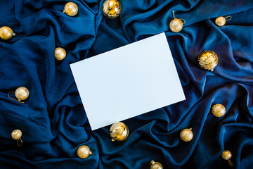Greetings background blue color silk cloth with golden Christmas tree ball, white paper and gift boxes Flat lay composition for greeting cards
