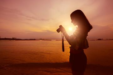 asian woman enjoy taking photo with camera on beach sunset twilight time
