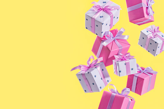 Flying gift box on yellow background. Concept of holiday, gift, sale. Birthday. Copy space.