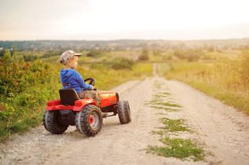 Child with a toy tractor on a trip. Wall mural