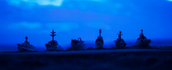 Military navy ships in a sea bay at sunset time. Selective focus