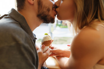 Romantic couple in love with ice cream kissing indoors in cafe. Selective focus on ice cream