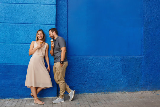 Happy couple having fun, eating ice cream and smiling against the blue wall