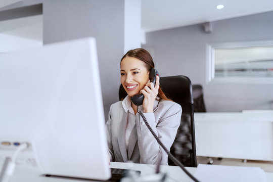 Gorgeous Caucasian businesswoman with long brown hair and in formal wear using computer and talking on the phone. Multitasking concept.