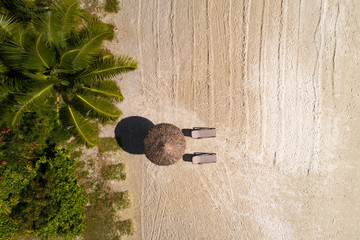 Aerial top view on the beach, umbrella and sand.
