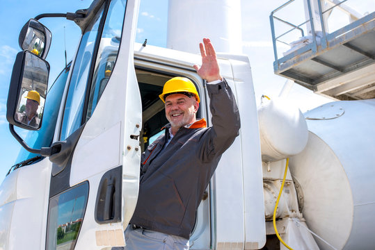 Concrete mixer truck driver with helmet enters the cabin of his truck