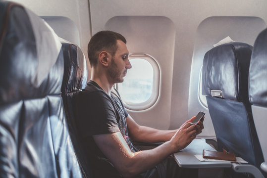 Man using a smartphone while flying in a plane.