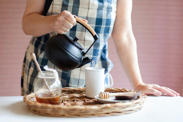 Woman is pouring tea from black cast iron teapot into mug. Tea time at kitchen table at cozy home. Jar of honey and cup are on straw wicker serving tray. Lifestyle moment.