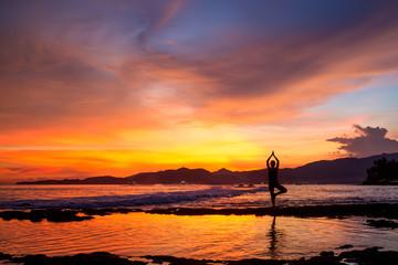 Caucasian woman practicing yoga at seashore Fototapete