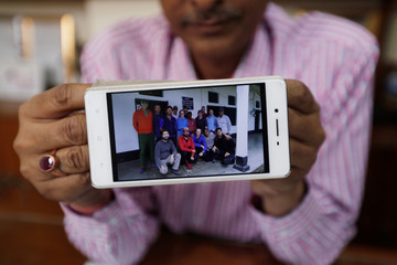 C.S. Pandey, Managing Director of the Himalayan Run & Trek Pvt. Ltd., shows a group photograph of the climbers before leaving for their expedition from Munsiyari town in the northern Himalayan state of Uttarakhand, at his office in New Delhi