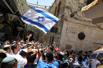 """Jewish youth wave an Israeli flag as they celebrate the annual """"Jerusalem Day"""" in Jerusalem's Old City"""