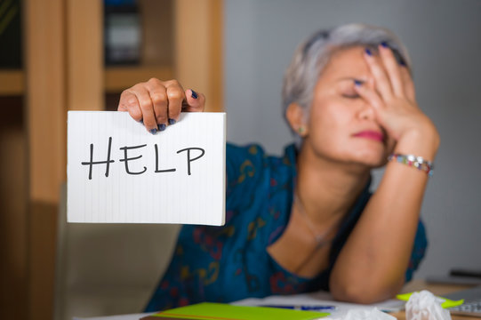 desperate and stressed attractive middle aged Asian woman holding notepad asking for help feeling overworked and exploited working at computer office desk suffering stress