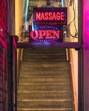 A 'Massage Open' sign hanging in the window of a massage parlour with blue and red LED lights.