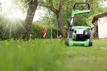 Mädchen spielt im Garten hinter Rasenmäher