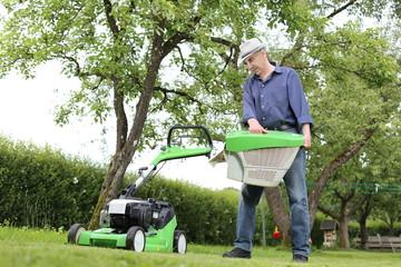 Mann am Rasenmäher mit Grasfangkorb