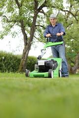 Mann beim Rasenmähen im Garten