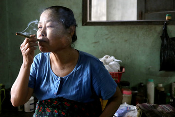 A woman smokes a cheroot, a traditional cigar from Myanmar in Bago