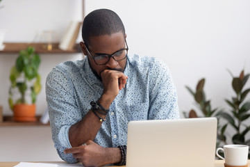 Head shot serious puzzled African American businessman looking at laptop Wall mural