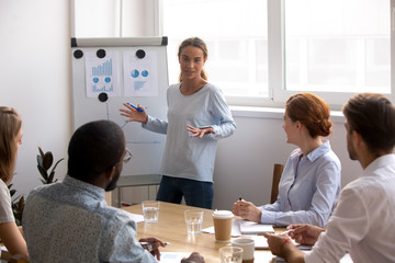Female business coach standing near whiteboard talking to diverse team