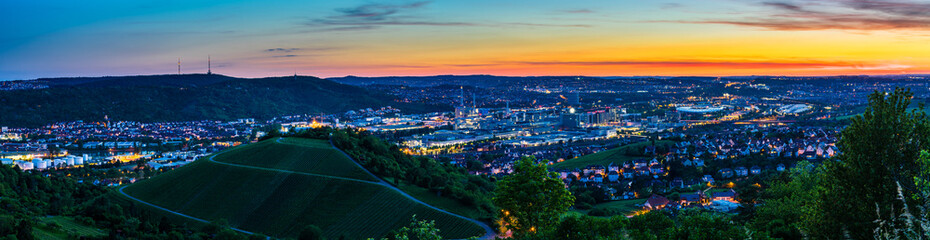 Germany, XXL landscape panorama of illuminated skyline of downtown city stuttgart at sunset from above in summer