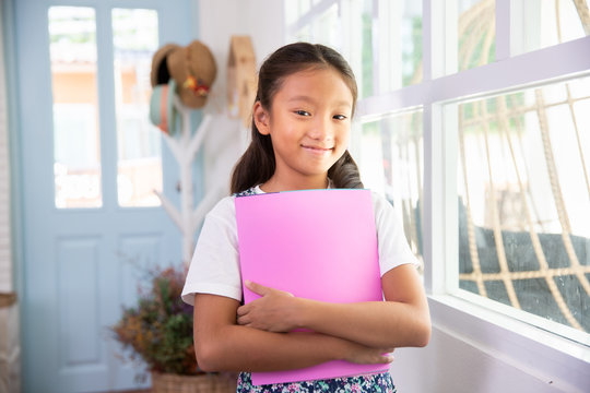 Little asian girl smiling and holding books at home