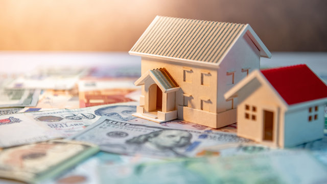 Real estate or property investment. Home mortgage loan rate. Saving money for retirement concept. House model on various of international banknotes on the table. Business finance background