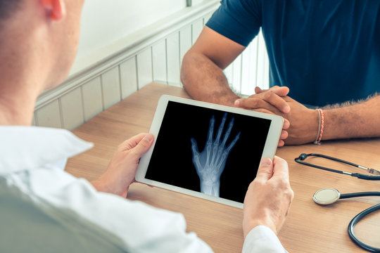 Doctor holding a digital tablet with x-ray of right hand of the patient