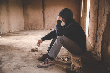 Men who show stress and loneliness, Homeless man drug  addict sitting alone and depressed  at an abandoned house feeling anxious and lonely, social documentary concept, Copy space