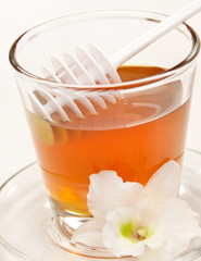 Honey and spoon with flowers