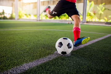 Soccer player speed run to shoot ball to goal on artificial turf.